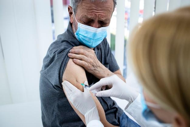 Zbliżenie na starszego mężczyznę szczepionego w ramię podczas pandemii wirusa koronowego.