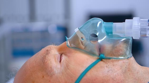 Zbliżenie na starszego mężczyznę z trudnościami w oddychaniu podczas noszenia maski tlenowej do oddychania. koronawirus covid-19 kryzys opieki zdrowotnej globalna pandemia, uzyskanie pomocy w walce z infekcjami dróg oddechowych we współczesnym świecie