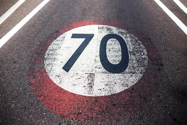 Zbliżenie na stary odrapany znak ograniczenia prędkości z 70 km na godzinę, namalowany na drodze asfaltowej.