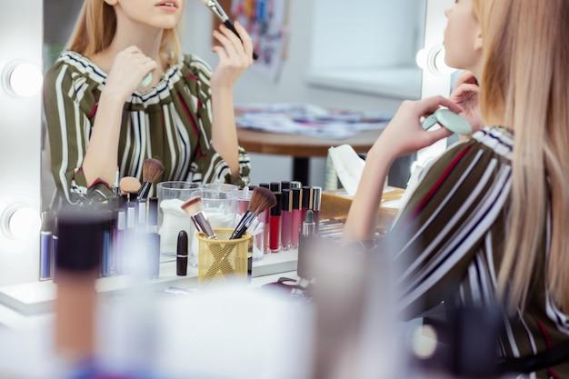 Zbliżenie na stół z mnóstwem leżących na nim kosmetyków