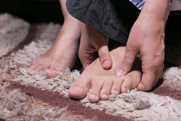 Zbliżenie na stopy kobiet i masaż dłoni w miejscu urazu