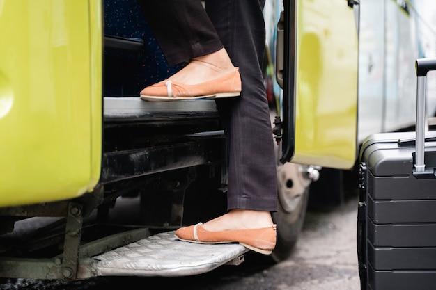 Zbliżenie na stopy kobiety w butach wspinającej się po schodach drzwi autobusu przed wyjazdem autobusem