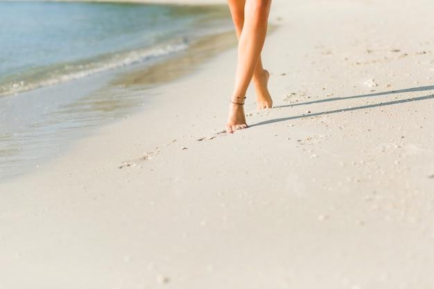 Zbliżenie na stopy opalonej szczupłej dziewczyny na piasku. idzie blisko wody. piasek jest złoty
