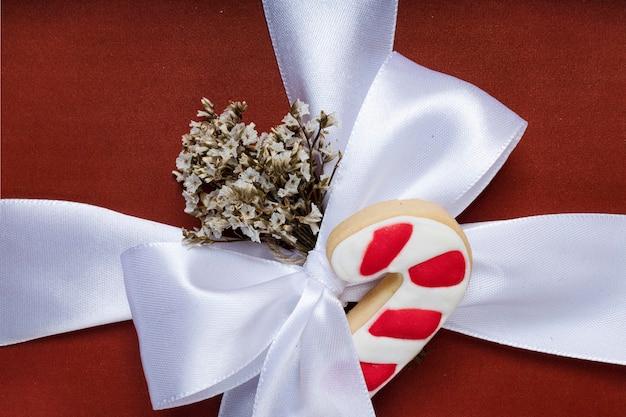 Zbliżenie na świąteczne lub noworoczne czerwone pudełko z białą wstążką i kawałkiem herbatnika z trzciny cukrowej