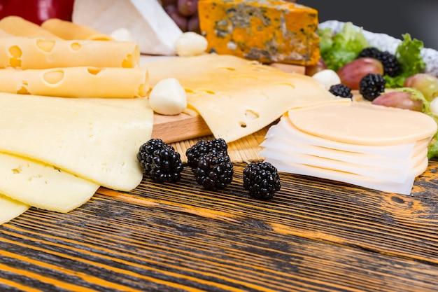 Zbliżenie na świeże jeżyny, udekorować na przystawkę dla smakoszy deska serowa podawane na rustykalnym drewnianym stole z miejsca na kopię