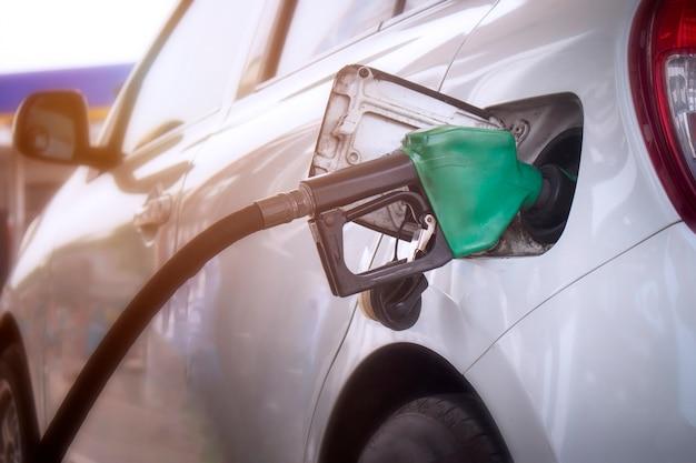 Zbliżenie na system monitorowania paliwa podczas tankowania ropy naftowej do pojazdu na stacji benzynowej.
