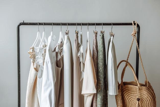 Zbliżenie na szafę z ubraniami wiszącymi na szynie na tle białej sceny w sklepie studyjnym