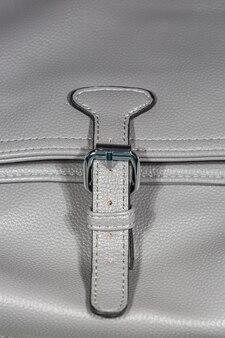Zbliżenie na szary detal torebki przedstawiający wzór klamry paska na klapie damskiej torebki