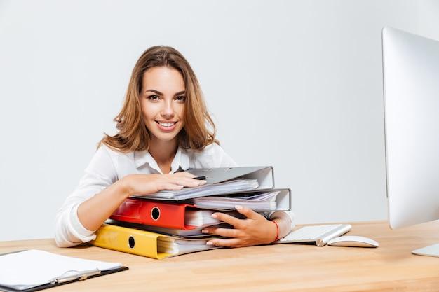 Zbliżenie na szczęśliwą bizneswoman trzymającą foldery siedząc przy biurku isoltaed na białym tle
