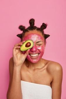 Zbliżenie na szczęśliwą kobietę etniczną cieszy się stosowanie maski na białym tle