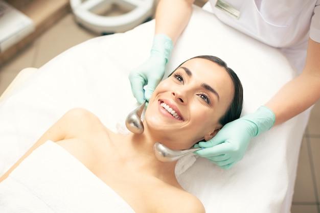 Zbliżenie na szczęśliwą młodą damę cieszącą się przyjemnym masażem za pomocą krio-kijków na szyi