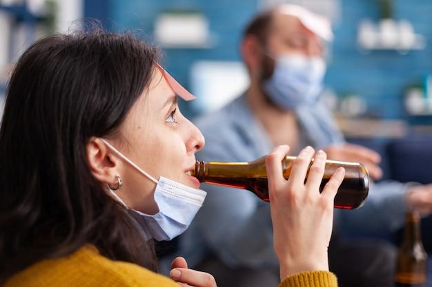 Zbliżenie na szczęśliwą wesołą kobietę pijącą piwo podczas grania w imię gry z wieloma etnicznymi przyjaciółmi o karteczki na czole noszące maskę, zachowując dystans społeczny. obraz koncepcyjny.
