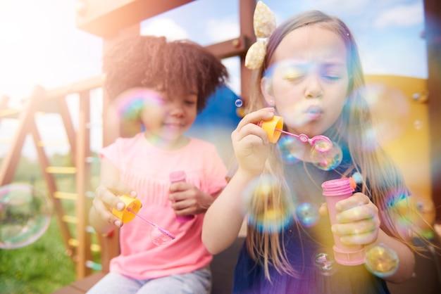 Zbliżenie na szczęśliwe dzieci bawiące się bańkami mydlanymi