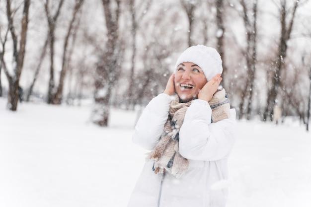 Zbliżenie na szczęśliwego dorosłego bawiącego się na śniegu