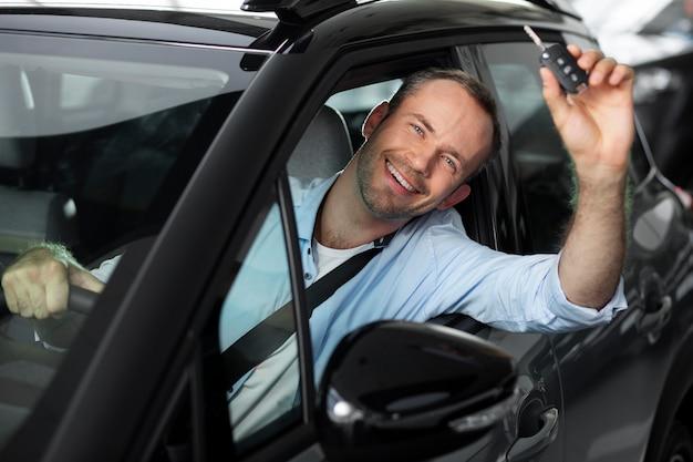 Zbliżenie na szczęśliwego klienta w salonie samochodowym