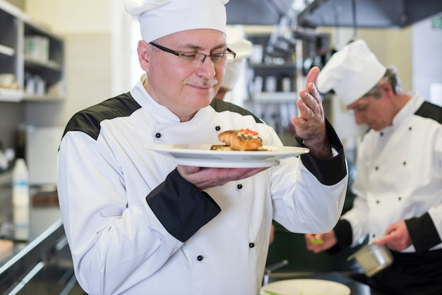 Zbliżenie na szefa kuchni wąchania potrawy po ugotowaniu