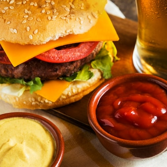 Zbliżenie na szklankę piwa z cheeseburgerem i sosem