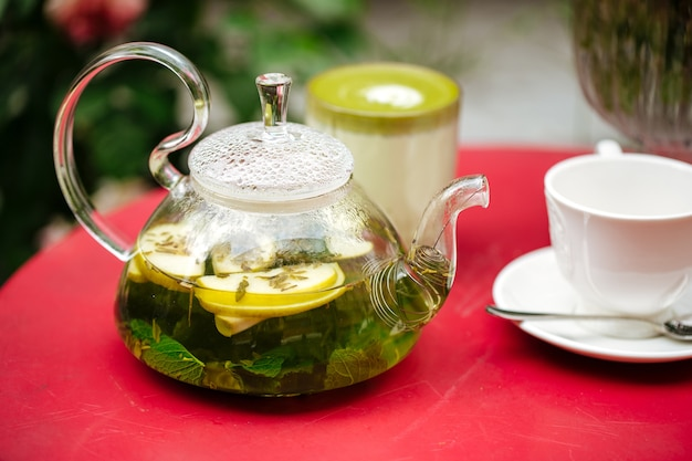 Zbliżenie na szklany imbryk z zielonej miętowej herbaty i filiżanki