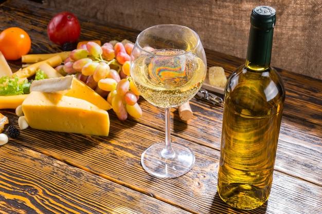 Zbliżenie na szkło i butelkę białego wina na rustykalnym drewnianym stole z różnych serów i winogron z miejsca kopii na pierwszym planie