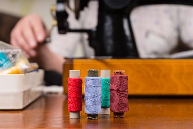Zbliżenie na szpule kolorowej nici na stole przed osobą korzystającą ze staroświeckiej ręcznej maszyny do szycia w tle