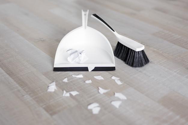 Zbliżenie na szufelkę, szczotkę i podarte kawałki papieru na podłodze