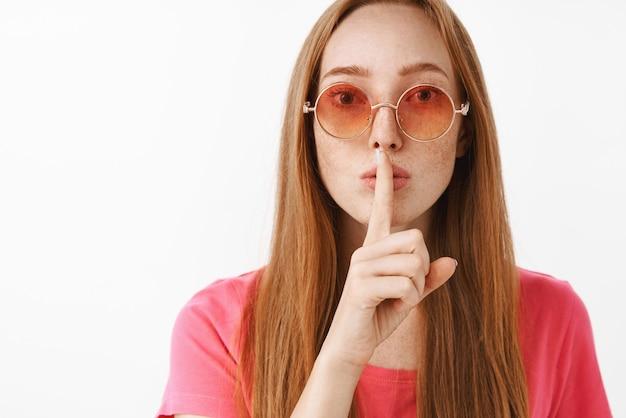 Zbliżenie na tajemniczą i poważną kobiecą atrakcyjną rudowłosą z piegami w stylowych okularach przeciwsłonecznych, mówiącą cii, prosząc o ciszę z gestem uciszenia, trzymając palec wskazujący na ustach