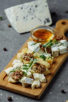 Zbliżenie na talerz serów. 4 rodzaje sera, miękki biały ser brie, camembert, półmiękkie brykiety, ser pleśniowy, roquefort, ser twardy. orzechy włoskie, zielone winogrona. piękny serwis. restauracja.