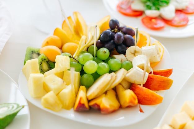 Zbliżenie na talerz z dużym asortymentem owoców. świętuje w restauracji.
