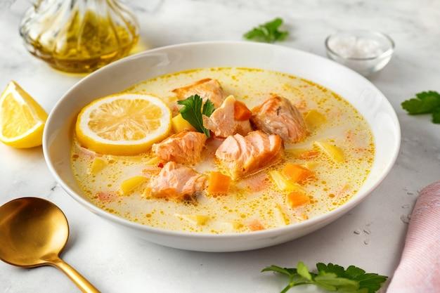 Zbliżenie na talerz z pyszną zupą rybną z łososia z kremem na bazie warzyw na białej powierzchni. pojęcie zdrowej diety