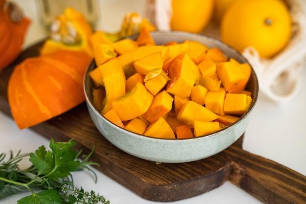 Zbliżenie na talerz z surowymi kawałkami dyni na stole w kuchni. pozytywny żółty backgorund. koncepcja jesień. święto dziękczynienia