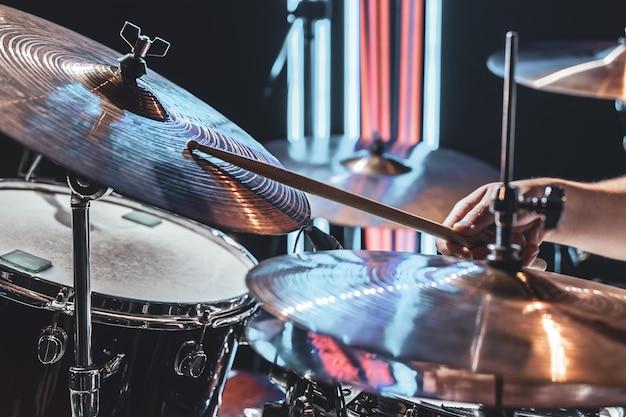 Zbliżenie na talerze perkusyjne, gdy perkusista gra z pięknym oświetleniem