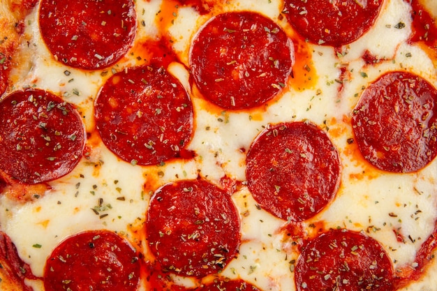 Zbliżenie na tle tekstury świeżej pizzy peperoni pieczone