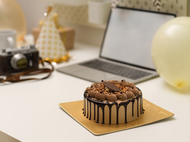 Zbliżenie na tort urodzinowy na stole z laptopem, aparatem i dekoracjami, koncepcja przyjęcia urodzinowego online