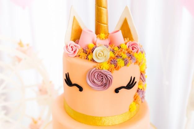 Zbliżenie na tort z motywem jednorożca ozdobionym kwiatami