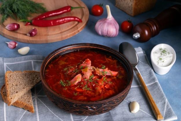 Zbliżenie na tradycyjny rosyjski barszcz zupowy z kapusty, buraków i innych warzyw podawany w glinianym talerzu ceramicznym z kwaśną śmietaną i czosnkiem. koncepcja kuchni narodowej. selektywne skupienie.