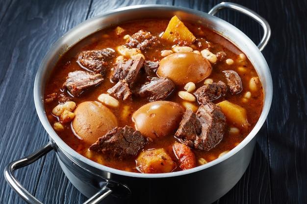 Zbliżenie na tradycyjny żydowski cholent (hamin) - główne danie na posiłek szabatowy wolno gotowanej wołowiny z ziemniakami, fasolą i brązowymi jajami w metalowej zapiekance na czarnym drewnianym stole