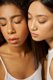 Zbliżenie na twarz dwóch pięknych młodych kobiet rasy mieszanej z idealnie świecącą skórą pozujących razem