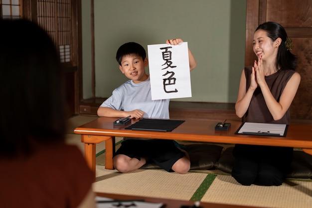 Zbliżenie na uczniów wykonujących japońską kaligrafię, zwaną shodo
