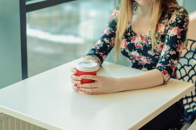 Zbliżenie na uroczą kobietę siedzącą przy stoliku w kawiarni przy oknie i pijącą gorącą kawę