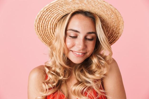 Zbliżenie na uroczą młodą blondynkę ubraną w letnią sukienkę i stojący kapelusz pozujący na białym tle na różowej ścianie