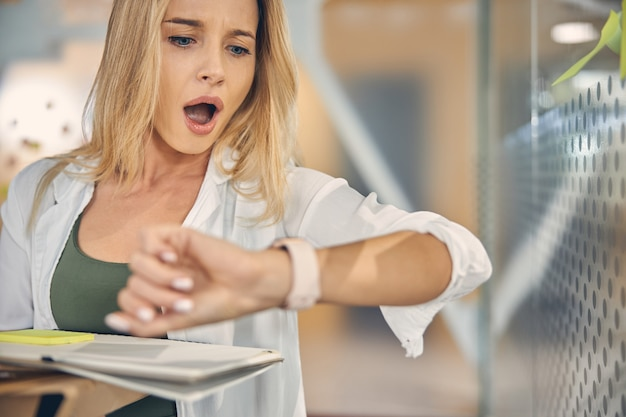 Zbliżenie na uroczą pracownicę patrzącą na zegarek w panice, trzymając papiery