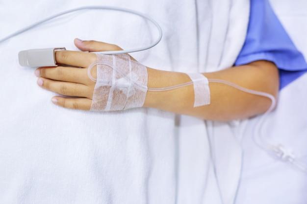 Zbliżenie na uścisk dłoni chorego pacjenta zachęca do leżenia na łóżku na oddziale szpitalnym.