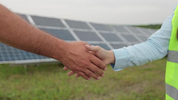 Zbliżenie na uścisk dłoni na tle panelu słonecznego. inżynierka podaje rękę z partnerem w porozumieniu. concept.energia odnawialna, technologia, elektryczność, usługi, zieleń.