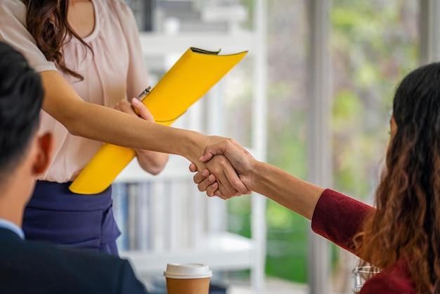 Zbliżenie na uścisk dłoni podczas rozmowy kwalifikacyjnej między młodą azjatką a dwoma menedżerami