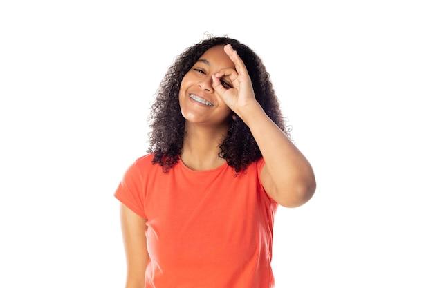 Zbliżenie na uśmiechający się african american kobieta na sobie czerwony t-shirt na białym tle.