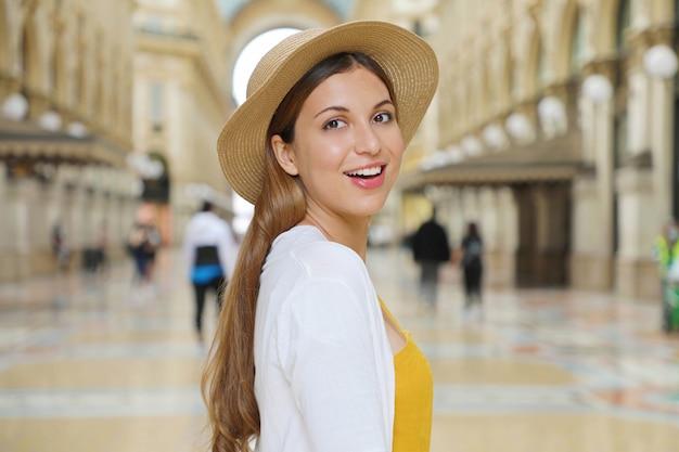 Zbliżenie na uśmiechniętą kobietę turystyczną mody, odwiedzając galerię vittorio emanuele w mieście mediolan, włochy