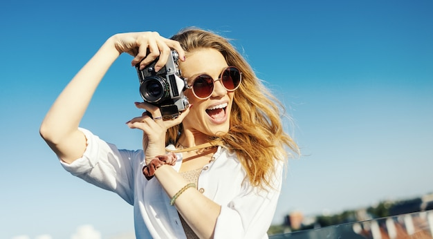 Zbliżenie na uśmiechniętą, modnie ubraną blond kobietę pozującą z aparatem