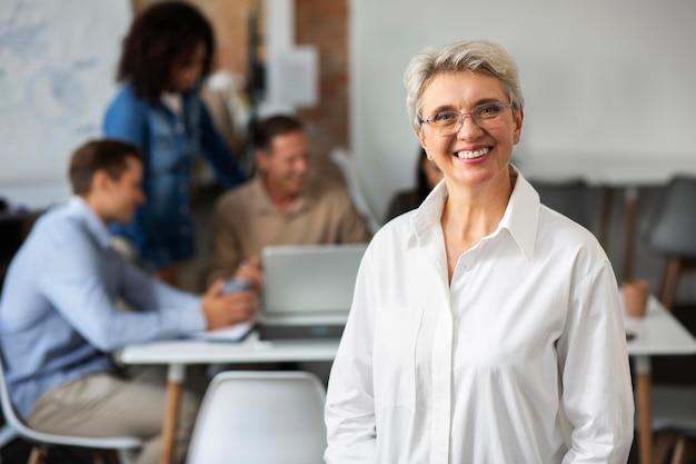 Zbliżenie na uśmiechniętą osobę w sali konferencyjnej