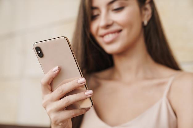 Zbliżenie na uśmiechniętą, piękną, młodą dziewczynę ubraną w letnią sukienkę, korzystającą z telefonu komórkowego na zewnątrz
