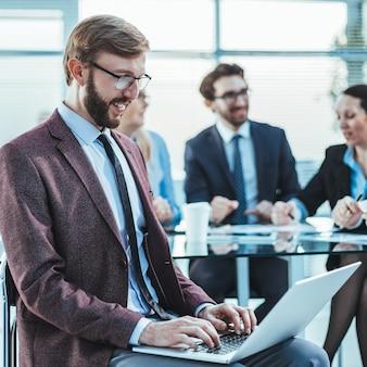 Zbliżenie na uśmiechniętego biznesmena korzystającego z laptopa w biurze